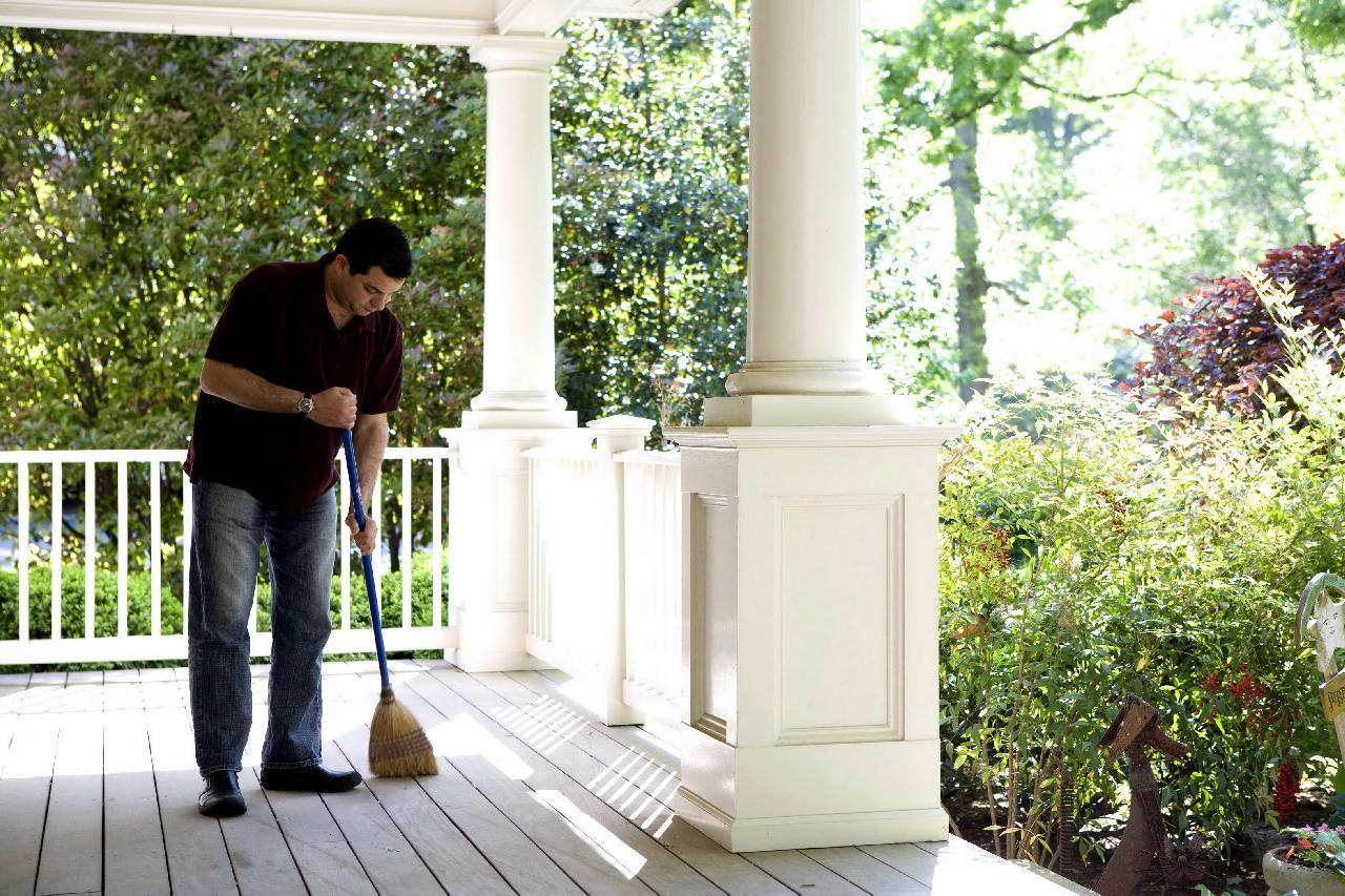 hombre barriendo porche blanco de casa