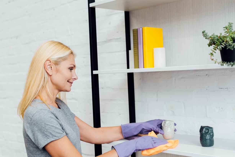 mujer rubia realizando la tarea de limpiar el polvo en una estantería